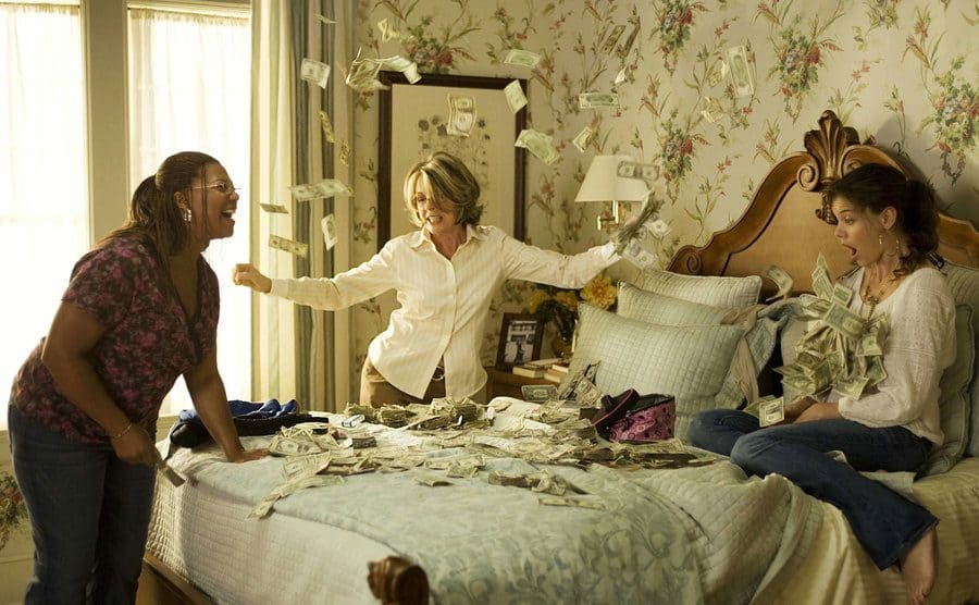 Katie Holmes, Queen Latifah, and Diane Keaton throwing money around on a bed