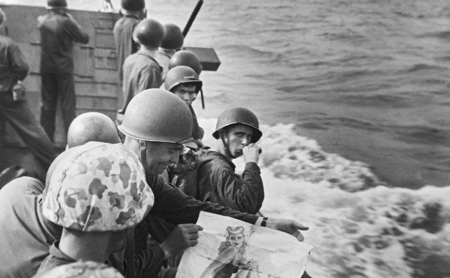 United States Marines on a landing barge share viewing a pinup girl as they approach the Japanese-held island of Tarawa.
