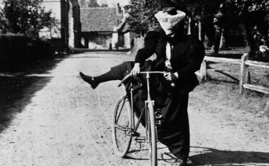 A lady is wearing a long skirt trying to get her leg over the saddle of her bicycle.