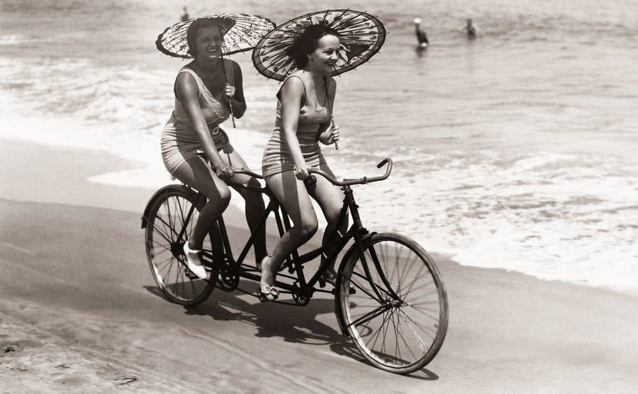 Two women enjoy a tandem bike ride down the beach with parasols in hand.