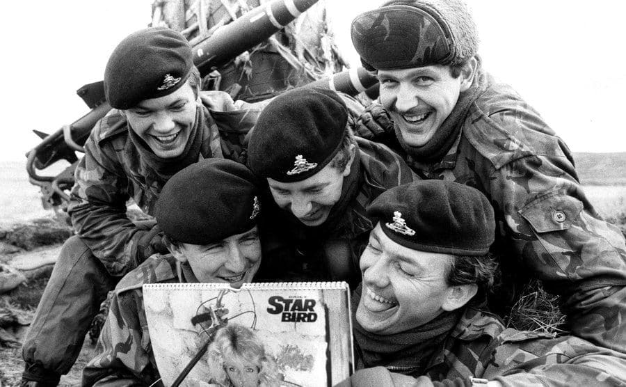 Soldiers piled on top of one another, trying to catch a glimpse at the girls on the calendar.