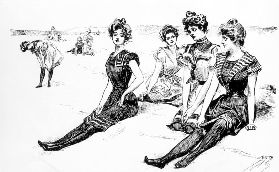 Women Wearing Swimsuits Seated at the Beach.