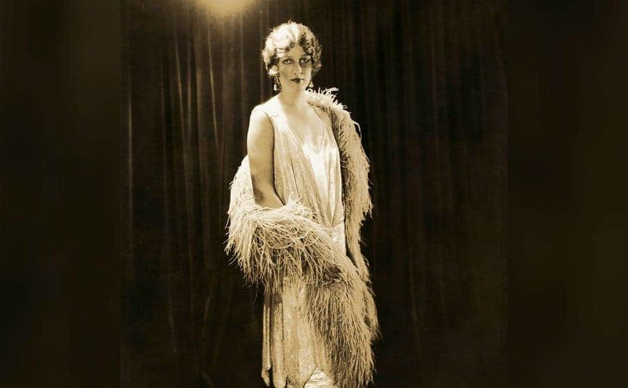 A woman models a loose-fitting sleeveless dress and feather boa typical of the Flapper style of the 1920s.