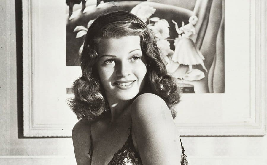 Rita Hayworth is posing for a photo in her bedroom while sitting on her bed.