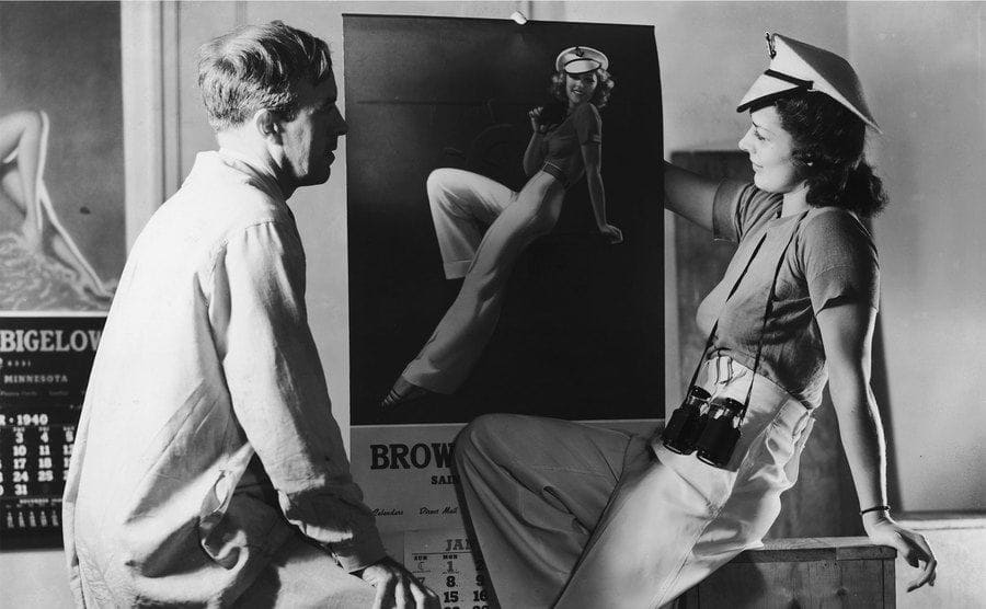 A model with her picture, painted for a Brown & Bigelow calendar by pinup artist Earl Moran