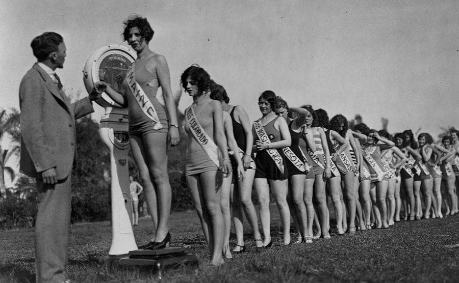 Contestants for Miss America Pageant getting weighed before the contest.