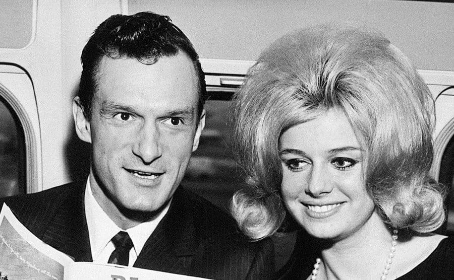 Hugh M. Hefner, Editor and Publisher of Playboy, is shown with Cynthia Maddox, the blond cover girl on the February issue of his magazine that he is holding.