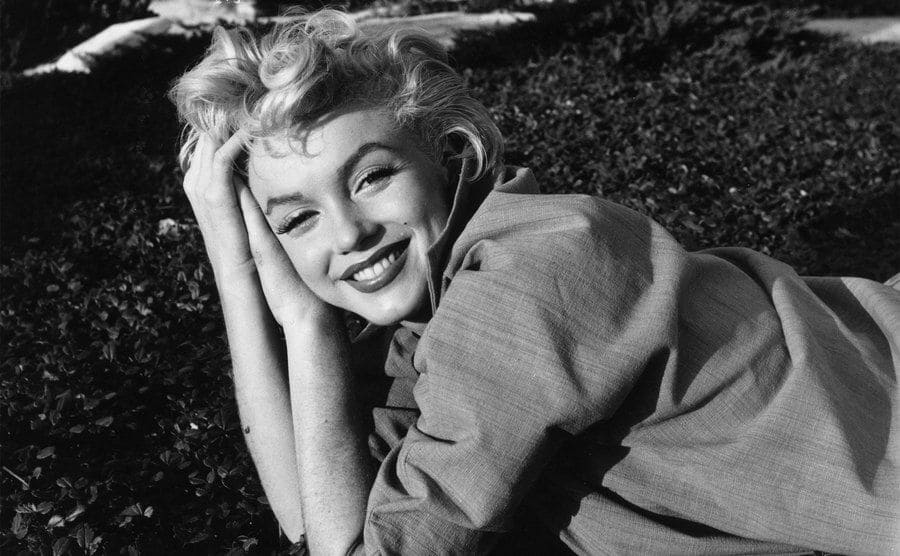 Marilyn Monroe is posing for a photo while lying on the grass.