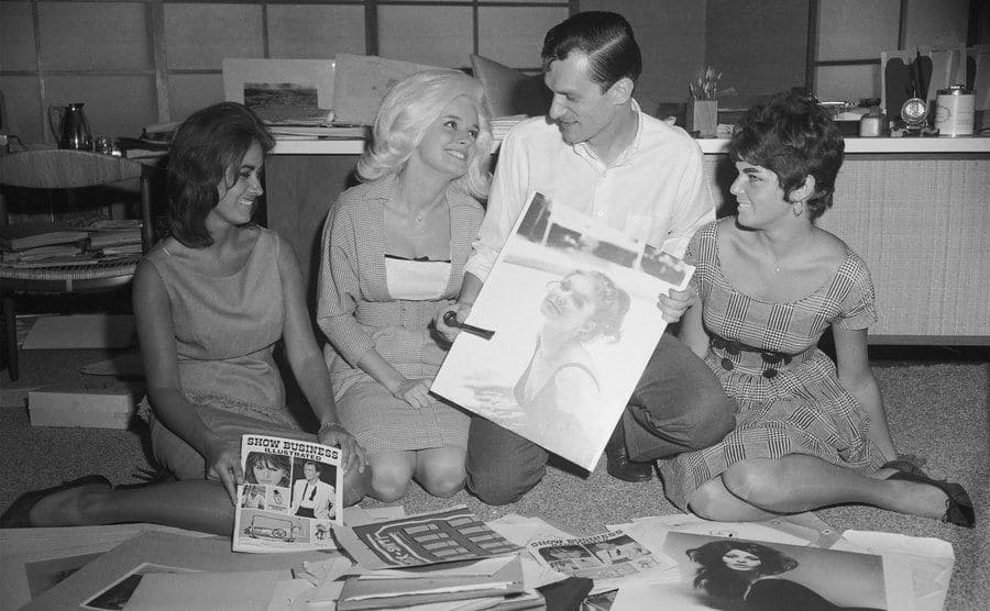 Hugh Hefner is sitting with women showing them images and articles as he tries to start his magazine.