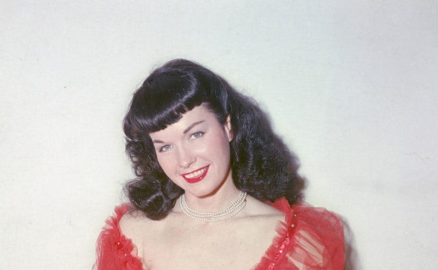 Bettie Page poses in a red negligee.