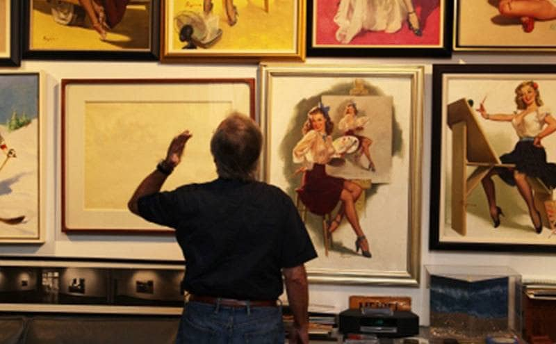 A man is standing before a collection of pinup girl pictures.