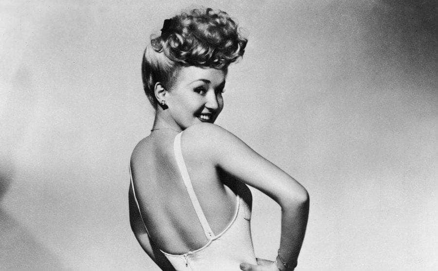 Betty Grable in high heels and a one-piece bathing suit and looks over her shoulder, one hand on her waist.
