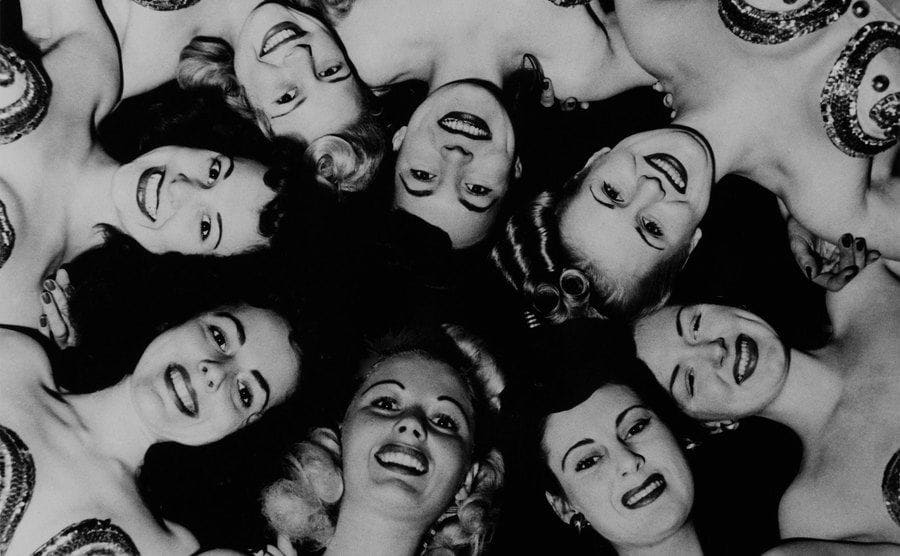 American Pinup girls are huddling their heads together for a photo.