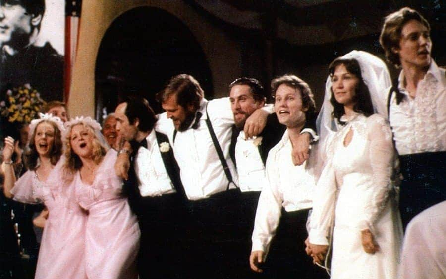 Robert De Niro And Christopher Walken celebrate with the rest of the wedding party in a scene from the film 'The Deer Hunter', 1978.