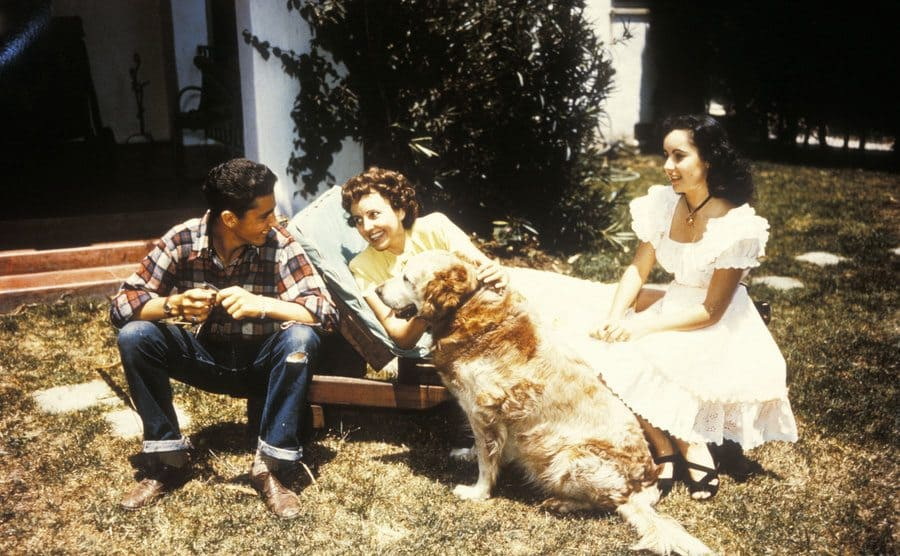 Sara Taylor and Elizabeth Taylor with their family dog and Edward Taylor sitting in their yard