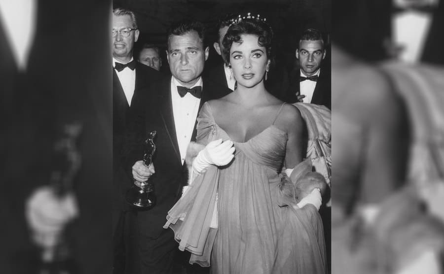 Mike Todd holding an Oscar and Elizabeth Taylor walking with him in a beautiful dress