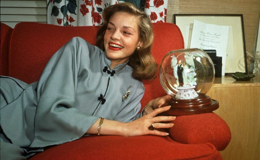 Lauren Bacall reclining across a red couch holding a snow globe with a bride and groom inside