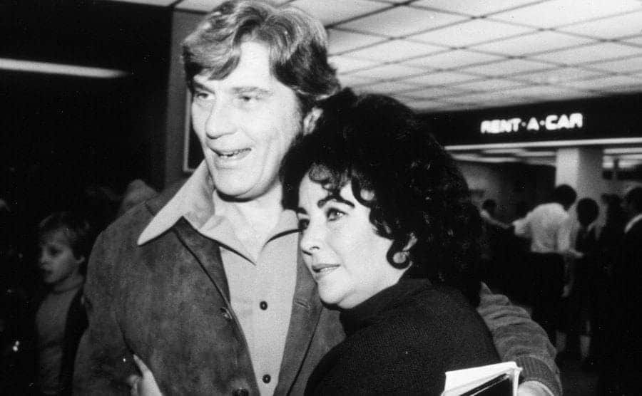 Elizabeth Taylor and John Warner outside of a Rent-A-Car store in 1976.