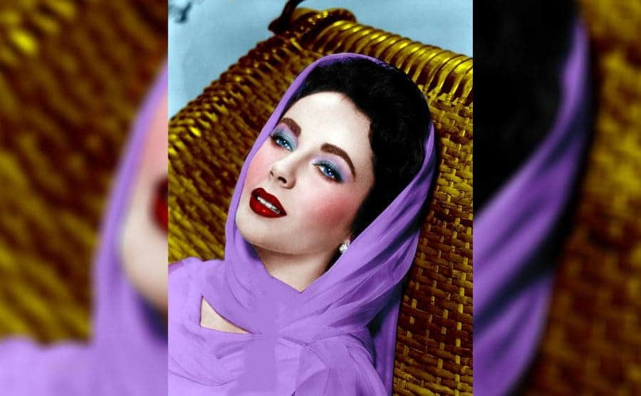 Elizabeth Taylor with a purple headscarf on and her eyes bright blue
