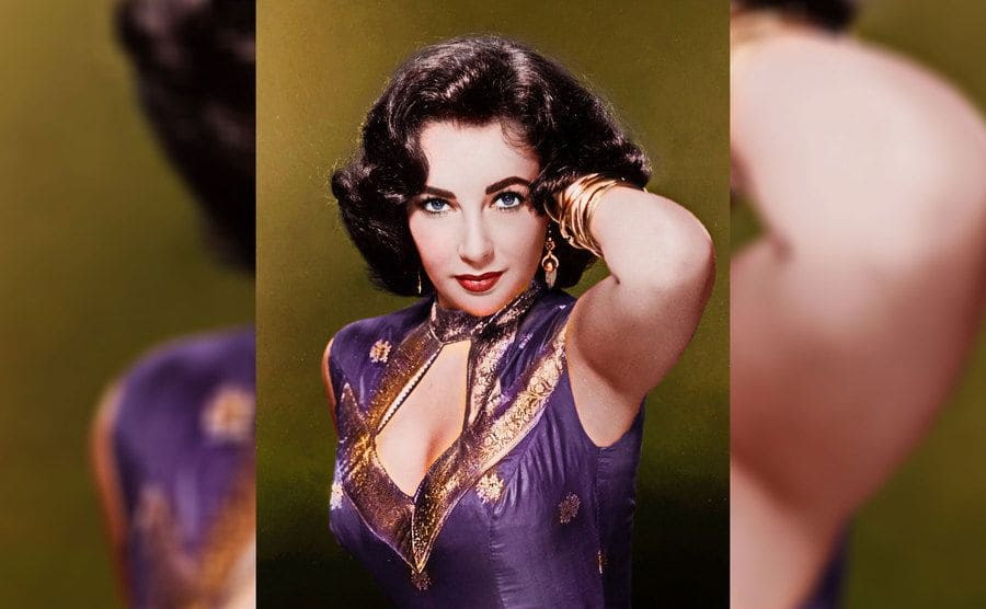 Elizabeth Taylor at a young age wearing a purple and gold dress