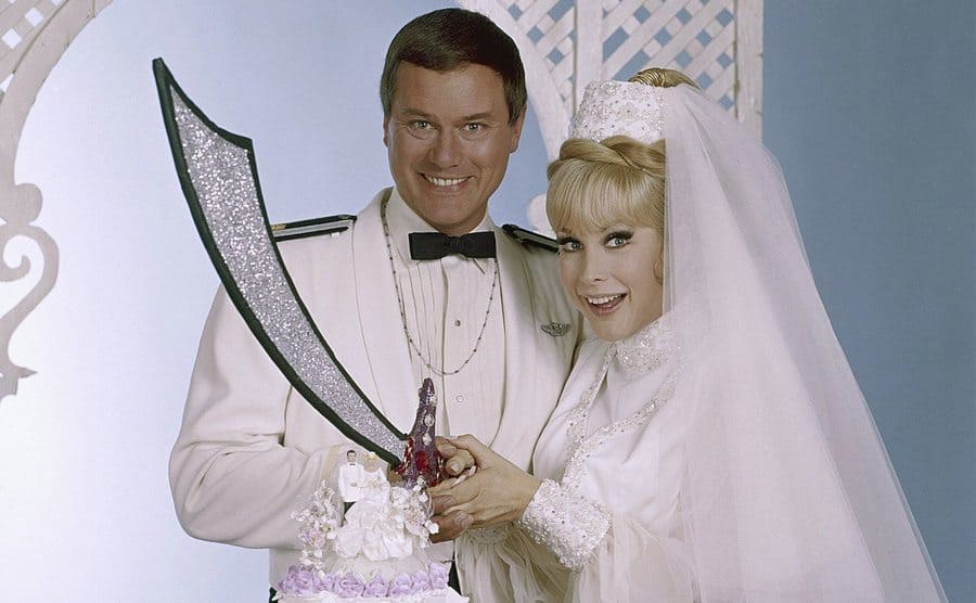 Nelson and Jeannie cut their wedding cake with a sword in a promo shot.