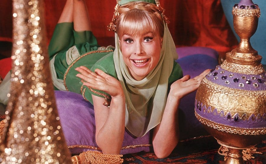 Barbara Eden holds her hands up and smiles while lying on top of oriental cushions.
