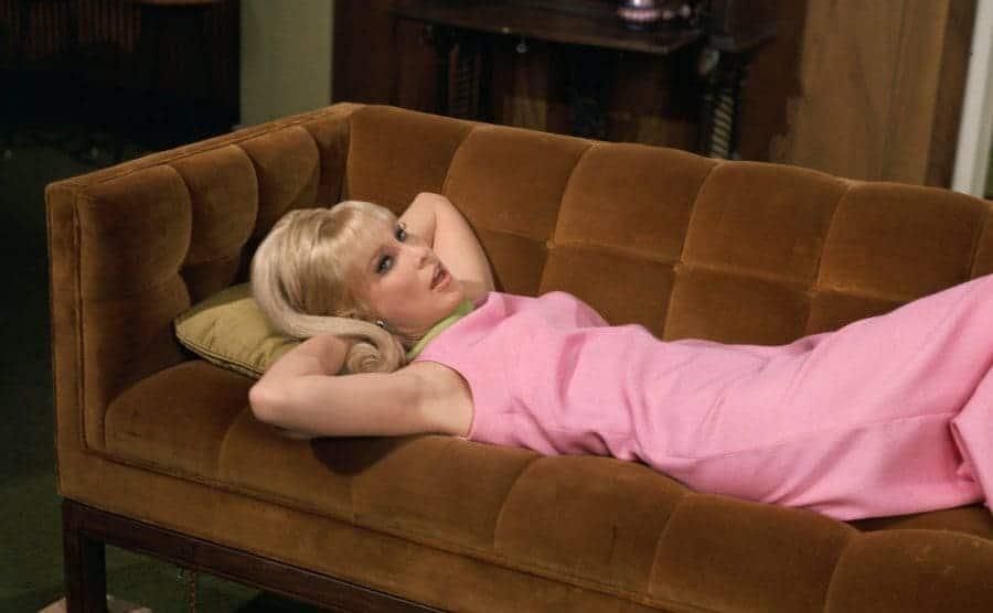 A TV still of Barbara Eden relaxing on the sofa wearing a long dress.