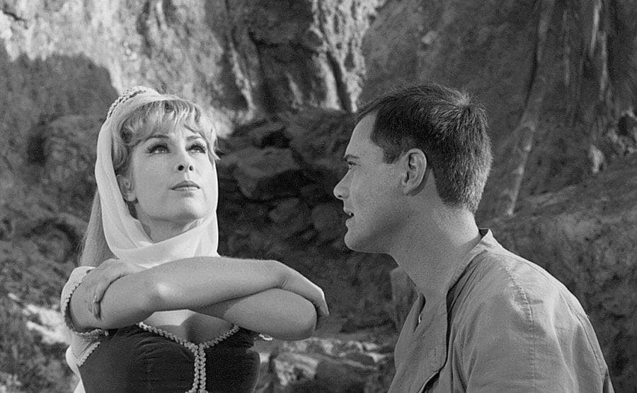 Barbara Eden and Larry Hagman and a rocky background in the pilot episode.