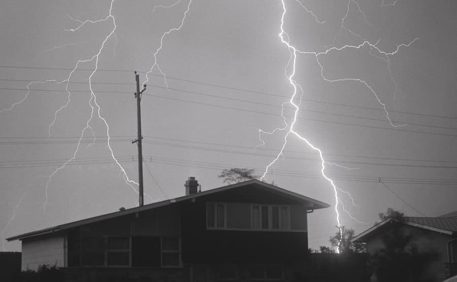 A lightning bolt discharges over the dark sky.
