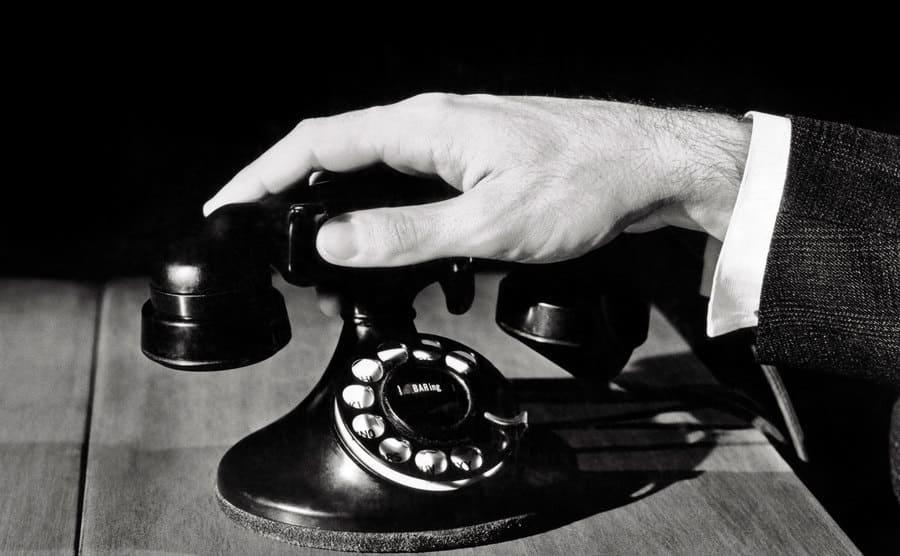 A male hand on a rotary telephone.