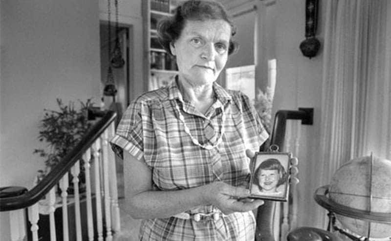 Beverly Burr stands holding a picture of Ann Marie.