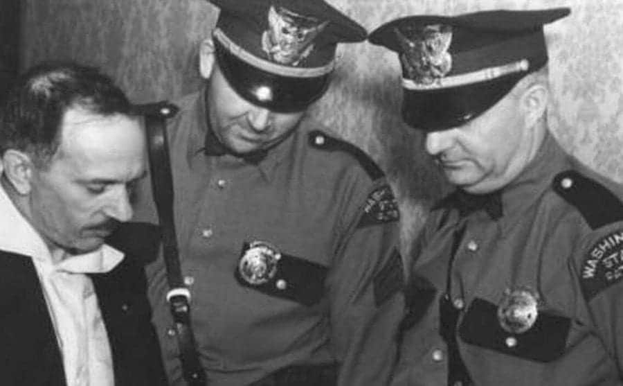 Two police officers talk to a detective.