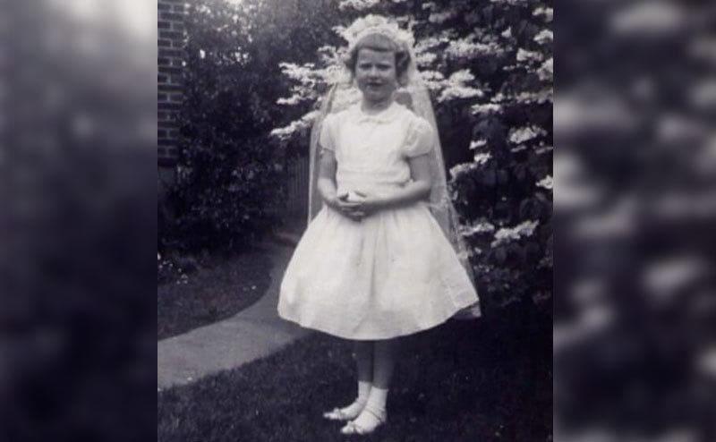 Ann Marie wears a white dress posing in the garden.