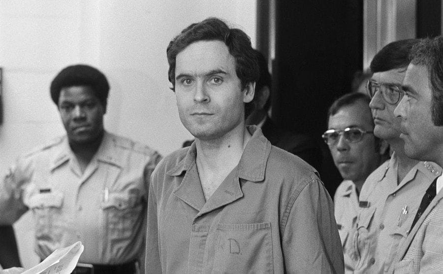 Police officers surround Ted Bundy at court.