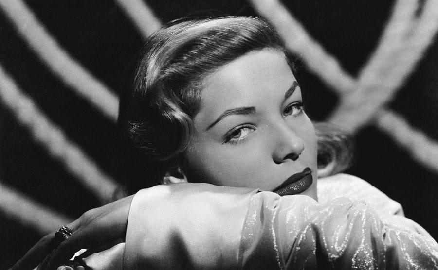 Lauren Bacall rests her head over her arm.