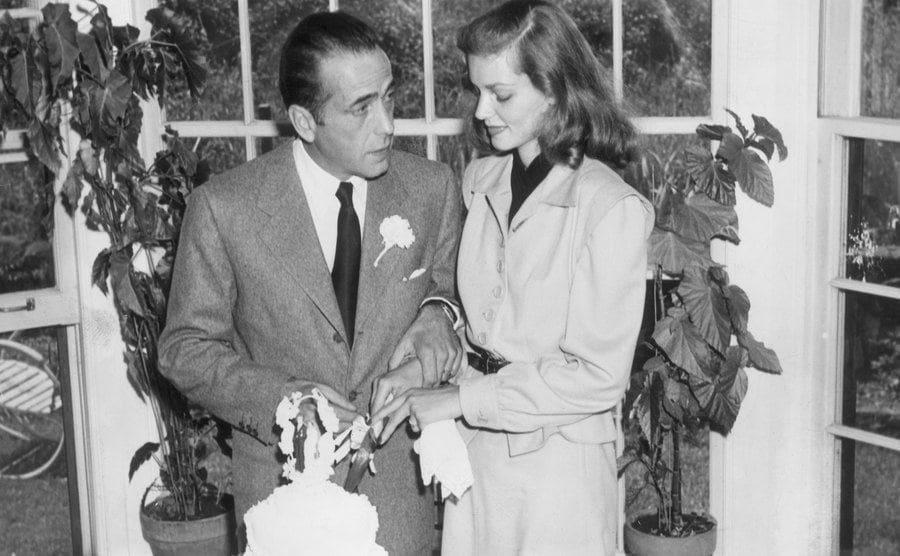 Bogart and Bacall cut their wedding cake.