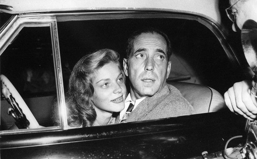 Bogart and Bacall in a convertible under the flashbulbs of photographers.