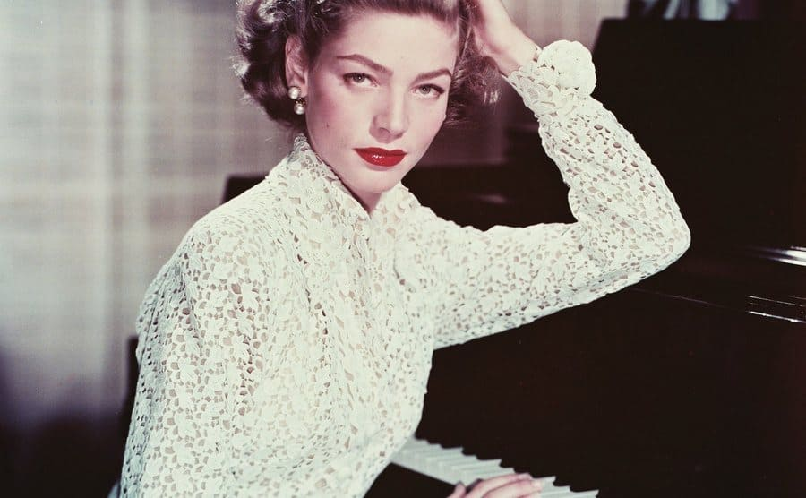 Lauren Bacall sits at home beside a piano.