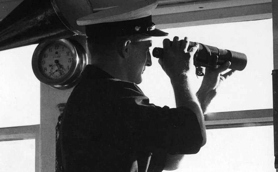 A Coast Guard is looking through a window with the telescope.