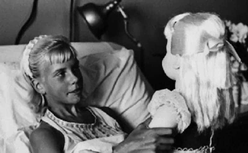 Terry Jo holds her doll while lying in bed.