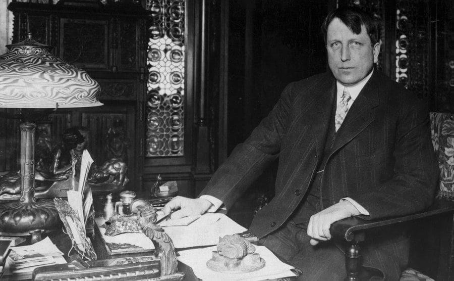 William Randolph Hearst sits on his desk.