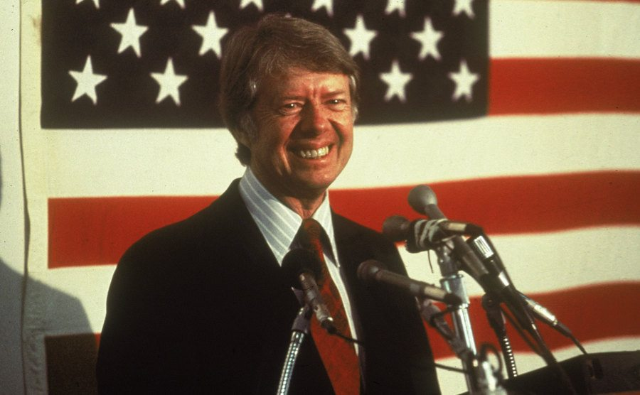Jimmy Carter stands in front of the U.S. Flag.