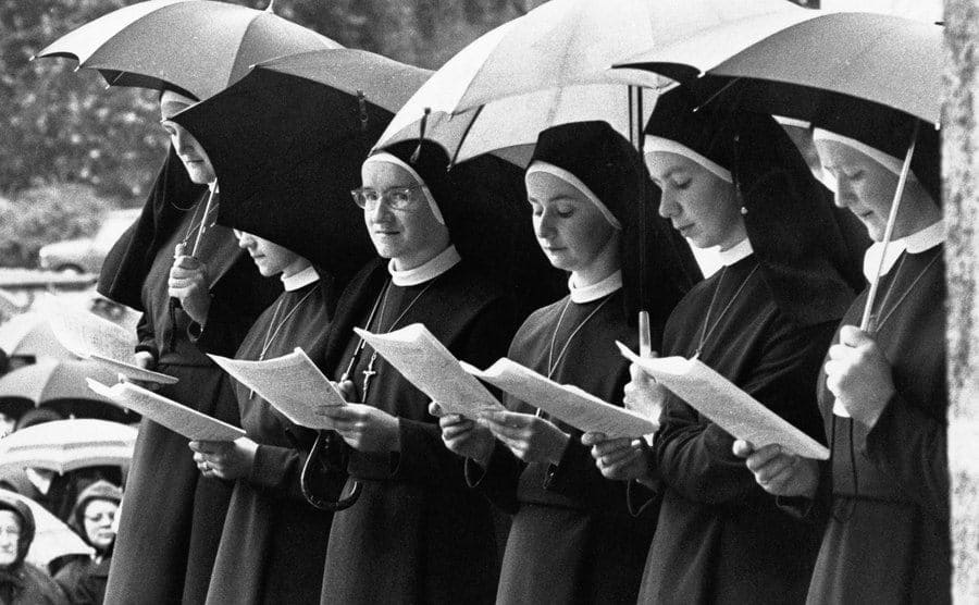 A group of nuns shelters under umbrellas to take their final vows.