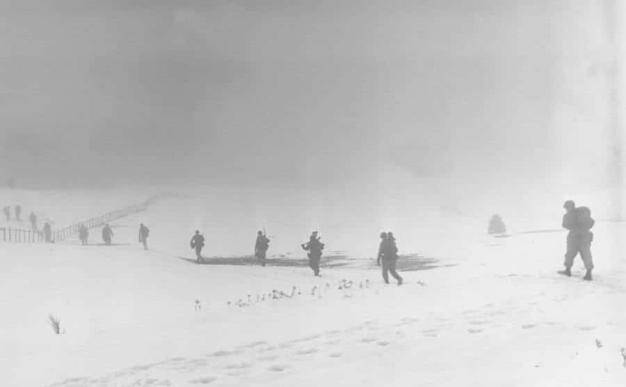 Soldiers are moving into the midst of a snowy field.