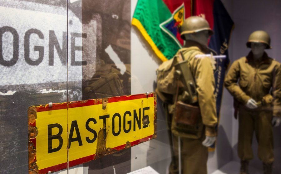 A bullet-riddled Bastogne town sign in a Museum.