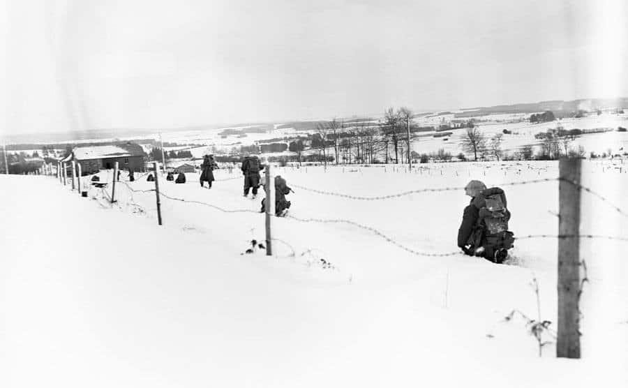 Soldiers slog through waist-deep snow.