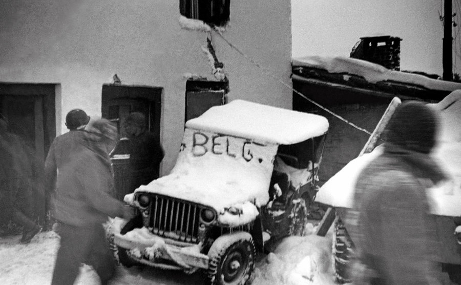 A snow-covered jeep with the word ''Belg'' on its windshield.