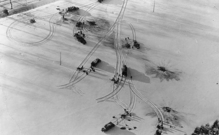 Military vehicles in a snowy field.