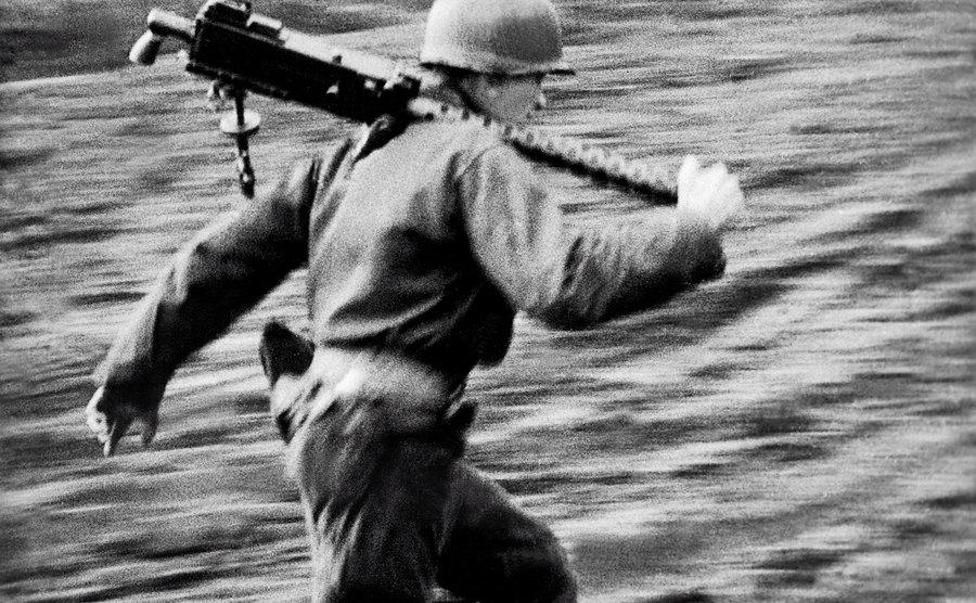 A soldier runs with a machine gun.