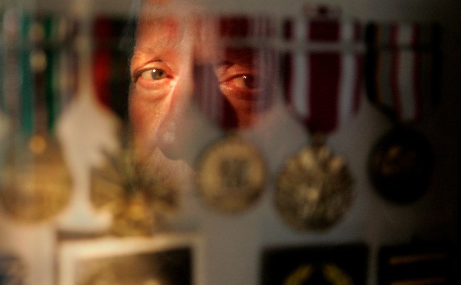 A war veteran is reflected in a glass case holding his war medals.